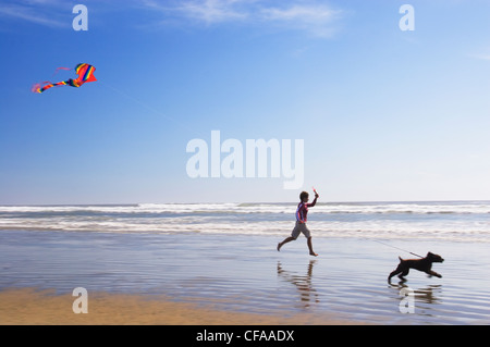 Girl and Cocker Spaniel dog running on Pacific Ocean beach with kite, Tofino, British Columbia, Canada. - Stock Photo