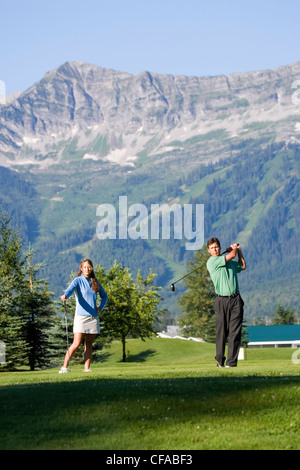 Young couple play golf at Fernie Golf and Country Club, Fernie, British Columbia, Canada. - Stock Photo