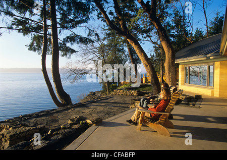 Couple sitting on deck of rammed earth house, Salt Spring Island, British Columbia, Canada. - Stock Photo