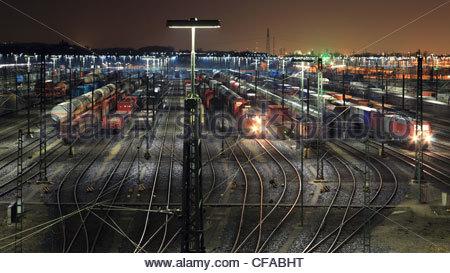 Train yard lit up at night - Stock Photo