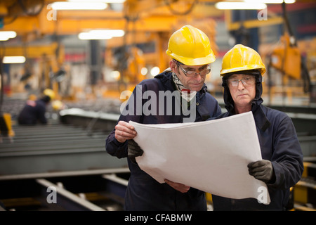 Workers reading blueprints in shipyard - Stock Photo