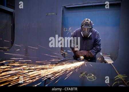 Steel cutter at work in shipyard - Stock Photo
