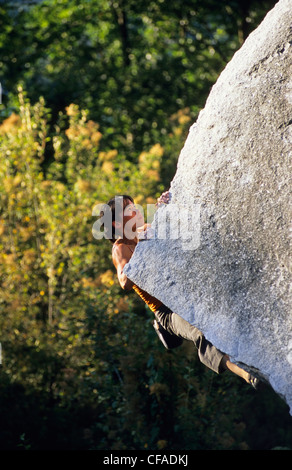Female bouldering on Cutting Edge, V4, Apron Boulders, Squamish, British Columbia, Canada. - Stock Photo