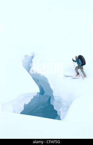 A skier encounters a crevasse during white-out navigation along the Leduc Glacier near Stewart, Yukon, Canada. - Stock Photo