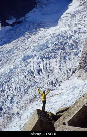 a young man enjoying the view of the foot of a glacier in the Bugaboo Range, British Columbia, Canada. - Stock Photo