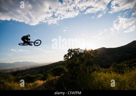 Mountain biker jumping on hillside - Stock Photo