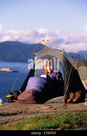 Woman reads a book in her tent, Lighthouse Park, West Vancouver, British Columbia, Canada. - Stock Photo