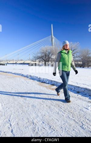 Motion blurred image of woman walking in winter. Esplanade Riel Bridge in the background. The Forks, Winnipeg, Manitoba, - Stock Photo