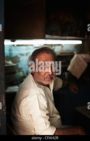 Middle-aged man sitting in shop - Stock Photo