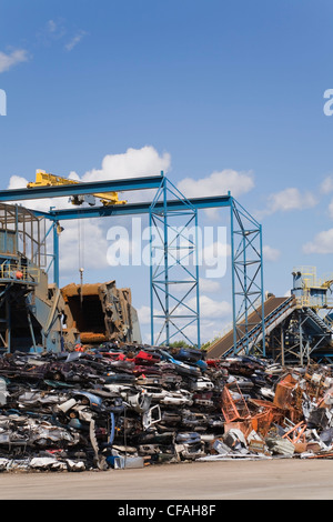Stacked and Crushed Automobiles and Industrial Metal Shredder at a Scrap Metal Recycling Junkyard, Quebec, Canada - Stock Photo