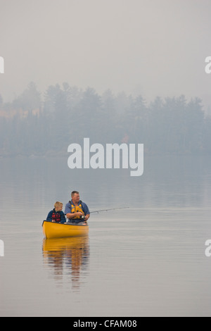 Young/middle-aged man fishing with son from canoe on Source Lake, Algonquin Provincial Park, Ontario, Canada. - Stock Photo