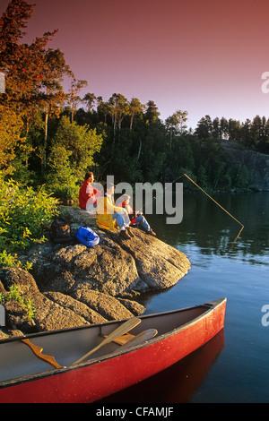 family relaxing along shoreline, boy fishing, Big Whiteshell Lake, Whiteshell Provincial Park, Manitoba, Canada - Stock Photo