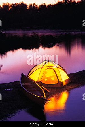 Silhouette of couple camping in tent on a riverbank, Whiteshell River, Whiteshell Provincial Park, Manitoba, Canada - Stock Photo