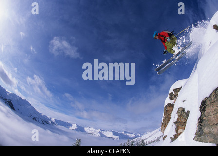 A female skier jumping a cliff in the backcountry of Kickinghorse Resort, Purcell Range, Golden, British Columbia, - Stock Photo