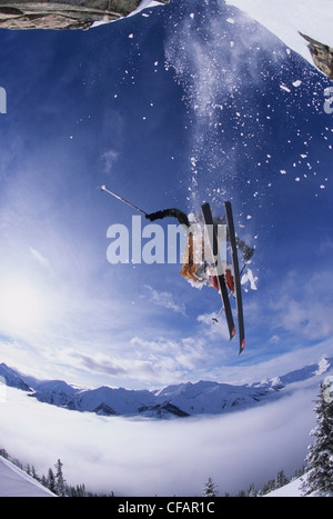 A skier catching some air after jumping a cliff in the backcountry of Kickinghorse Resort Area, Golden, British - Stock Photo