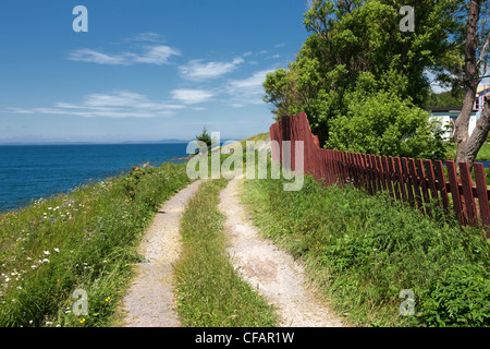 Clay road and fence along coastline in New Perlican, Newfoundland and Labrador, Canada. - Stock Photo