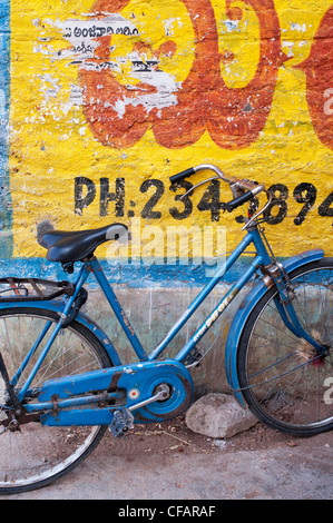 Traditional Indian womans bicycle against a yellow painted wall. Andhra Pradesh, India - Stock Photo