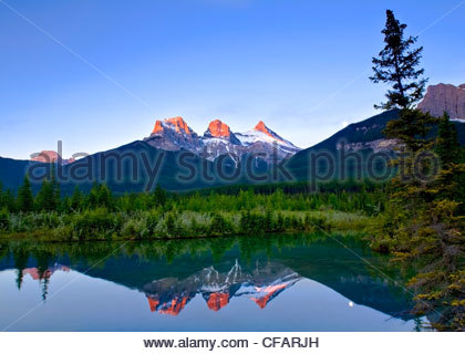 Three Sisters Mountain reflection in water, Canmore, Alberta, Canada - Stock Photo