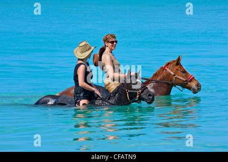 View of Buccoo Bay, Tobago with horse-riders in sea - Stock Photo