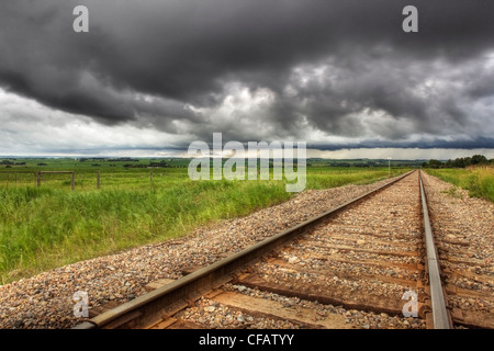 Railroad tracks with storm clouds in the background near Didsbury, Alberta, Canada - Stock Photo