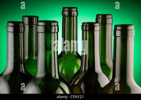 Wine bottle necks back lit on green - Stock Photo