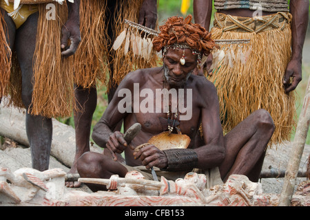 Man from the Asmat Tribe carving with a chisel, Agats village, New Guinea, Indonesia - Stock Photo