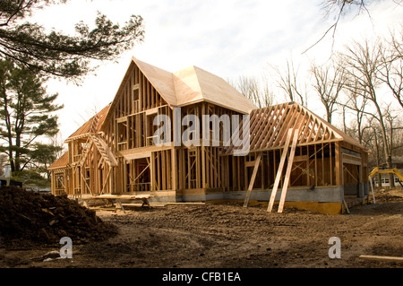Large McMansion type house under construction in framing phase - Stock Photo