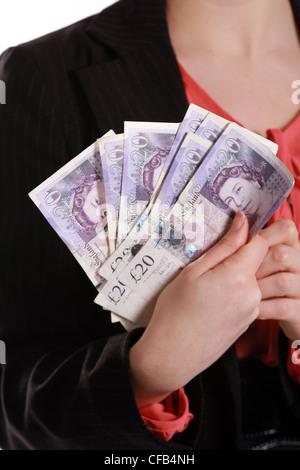 Woman holds a bundle of British Twenty pound notes - Stock Photo