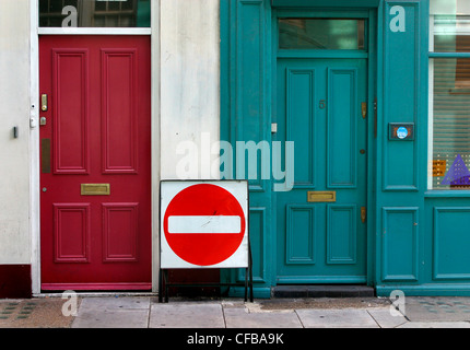 London street: no entry traffic sign on pavement between two houses - Stock Photo