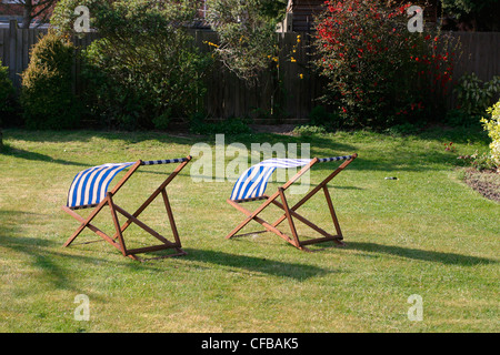 London suburbs: two empty blue and white striped deckchairs in gardenon grass lawn - Stock Photo