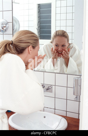 Back view of female long wavy blonde hair in ponytail wearing white dressing gown splashing water onto face over - Stock Photo