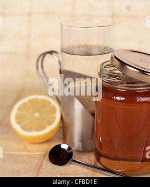 Silver mug steamed glass containing hot water and a lemon slice next to half opened jar of honey half a lemon and - Stock Photo