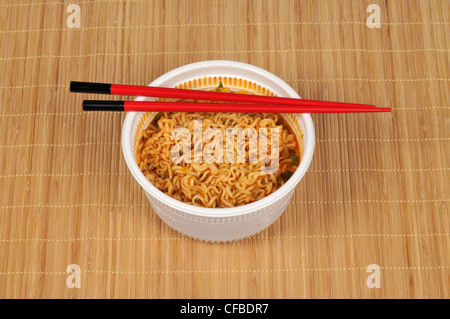 Bowl of oriental noodles with chopsticks on bamboo mat - Stock Photo