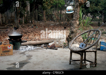 A wood burning stove and a chair on a patio comprise the backyard of a typical concrete home in Luang Namtha, Laos. - Stock Photo