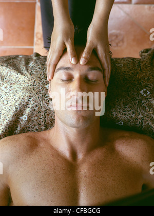 Couple at Spa in Northern Thailand: View from above of male lying on back having forehead massaged by female masseuse - Stock Photo