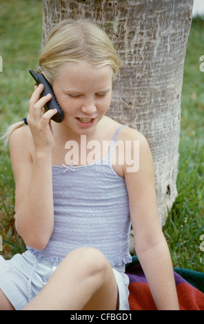 MFemale child blonde hair in two plaits wearing vest top and shorts sitting on blanket against tree trunk talking - Stock Photo