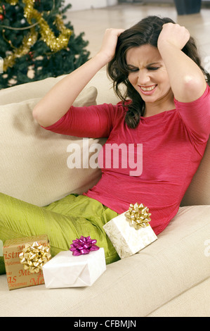 Female brunette wavy hair wearing bright pink top, lime green silk trousers, sitting on sofa presents, pulling at - Stock Photo