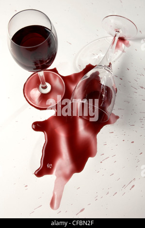 Glass of red wine on side, wine spilling out - Stock Photo