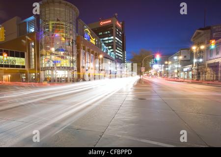 Traffic light trails and MTS Centre Arena at night. Portage Avenue, Winnipeg, Manitoba, Canada. - Stock Photo