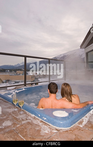 A young couple enjoy a relaxing soak and a glass of wine while hottubbing at dusk in Jasper, Alberta Canada - Stock Photo