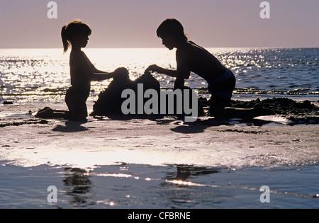 children building a sand castle, Grand Beach Provincial Park, Lake Winnipeg, Manitoba, Canada - Stock Photo