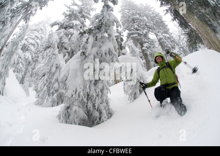 Young woman snowshoeing on the First Lake Trail at Seymour Mountain. North Vancouver, British Columbia, Canada - Stock Photo