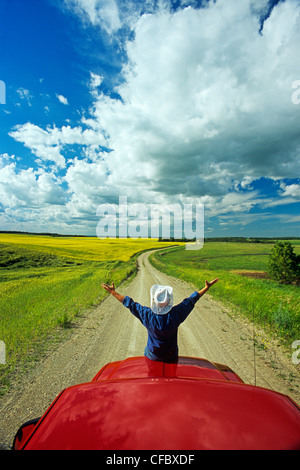 Man sits on the front of apick-up a truck on a country road with farmland in the background, Tiger Hills, Manitoba, - Stock Photo