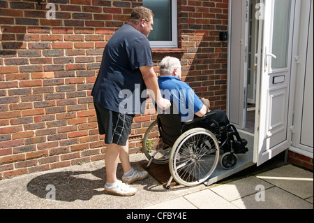 male carer / son pushing elderly man in wheelchair on ramp access to property - Stock Photo