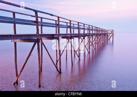 Wooden pier at dusk on Lake Winnipeg. Matlock, Manitoba, Canada. - Stock Photo