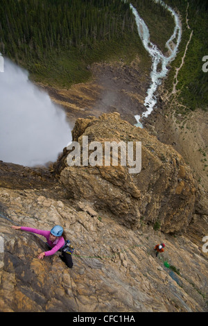A female rock climber ascends the Takakkaw Falls route (5.6) in Yoho National Park, BC - Stock Photo