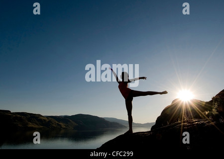 A silouetted female dancer trains over Kamloops lake at sunset, Kamloops, British Columbia Canada - Stock Photo