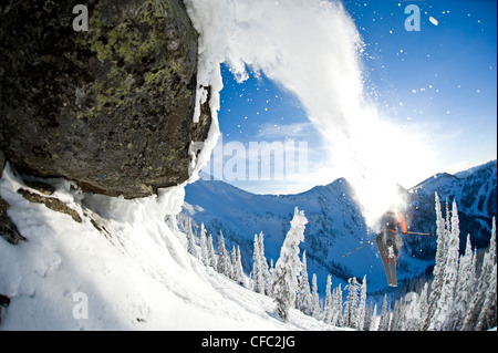 A male skier full of testosterone launches off a jump at Whitewater Winter Resort, Nelson, British Columbia - Stock Photo