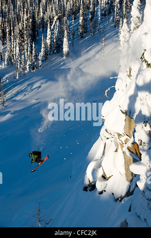 A male skier takes a huge jump off a cliff in the Whitewater Winter Resort backcountry, British Columbia - Stock Photo
