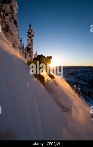 A female skier descends a slope at sunset in the Whitewater Winter Resort backcountry, British Columbia - Stock Photo